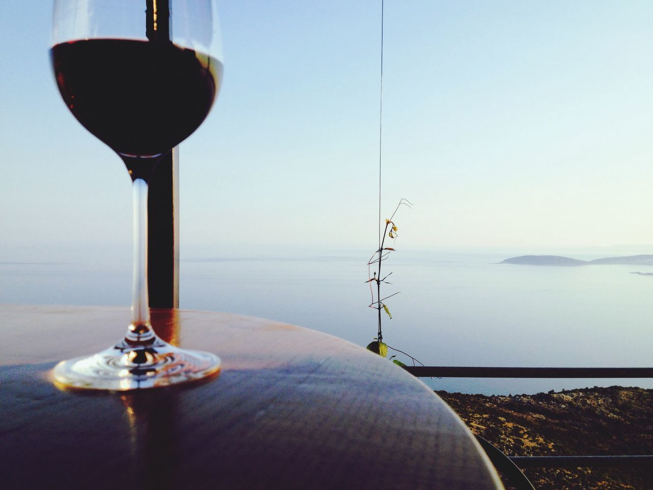 Close-Up Of Red Wine On Table Against Clear Sky