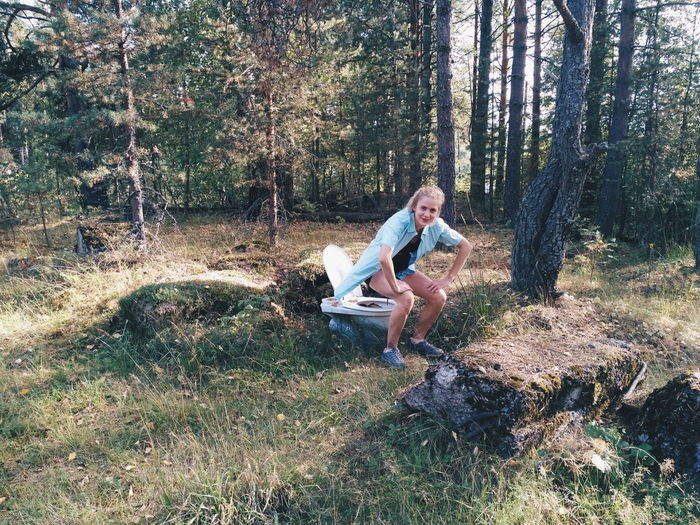 Woman In Chair Position Over Abandoned Toilet Seat In Forest