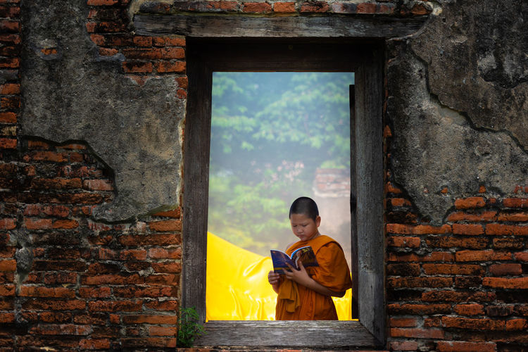 Boy wearing traditional clothing reading book seen through window