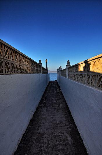Surface level of bridge against clear blue sky