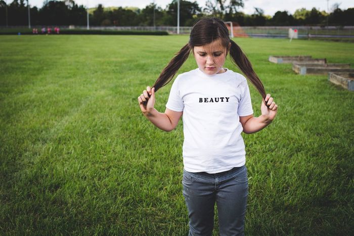 Child Girls One Person One Girl Only Grass People Children Only Casual Clothing Long Hair Front View Standing T-shirt Childhood Outdoors Looking At Camera Lifestyles Portrait Day Nature Real People Beauty Words Tshirt Tee Pigtails