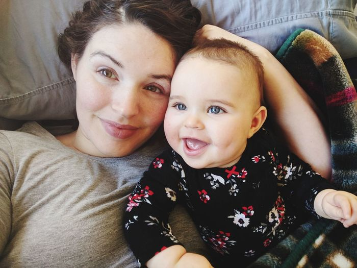 Portrait of mother lying with cheerful toddler daughter on bed