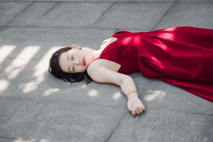 High angle portrait of woman lying down on floor