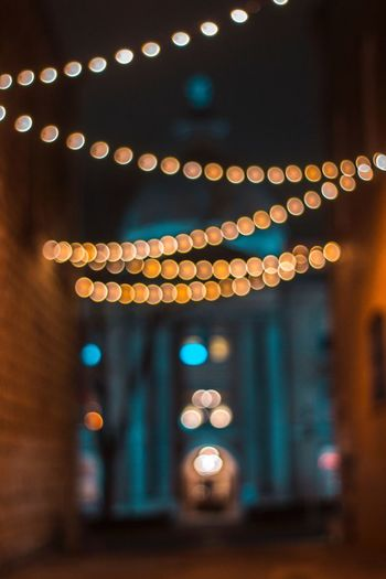 Defocused image of illuminated string lights hanging at alley