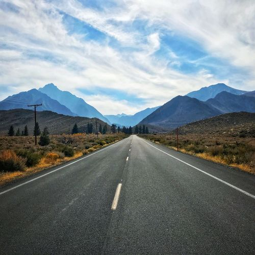 Empty road by mountains against cloudy sky