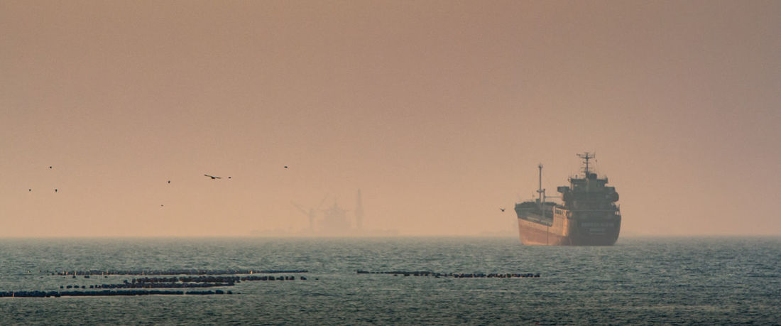 Cargo ship in sea with mist sky Cargo Ship Nature Tranquility Travel Weather Beauty In Nature Boat Day Horizon Over Water Mist Nature Nautical Vessel No People Outdoors Sea Sea And Sky Seascape Season  Sky Sunset Tranquil Scene Transportation Water