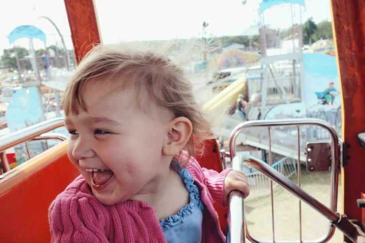 her first ride. Innocence Focus On Foreground Amusement Parks Carnival Fair Country Fair Amusement Park Rides Happy Expression Of Joy Smiling Face Hair Blowing In The Wind Young Girl People And Places Live For The Story
