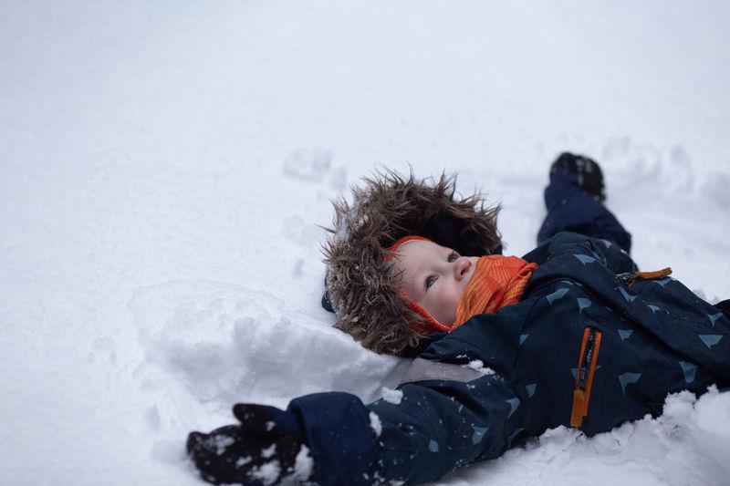 Boy lying in snow