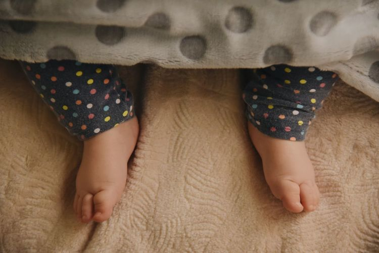 Low section of baby feet lying on bed under blanket