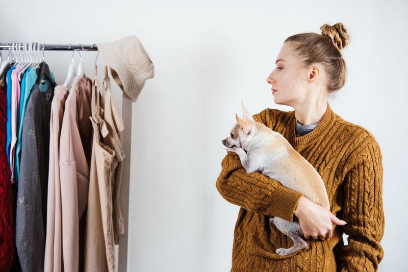 Beautiful woman with dog looking at garments