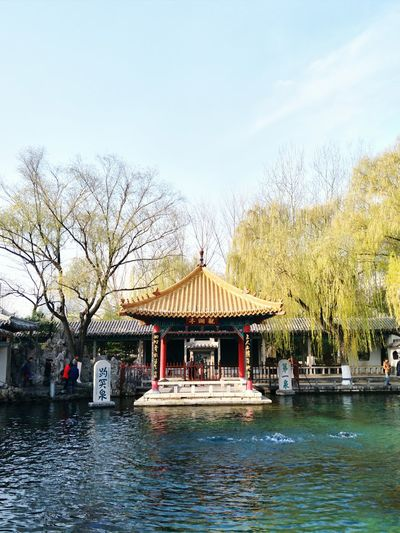 Temple by lake against sky