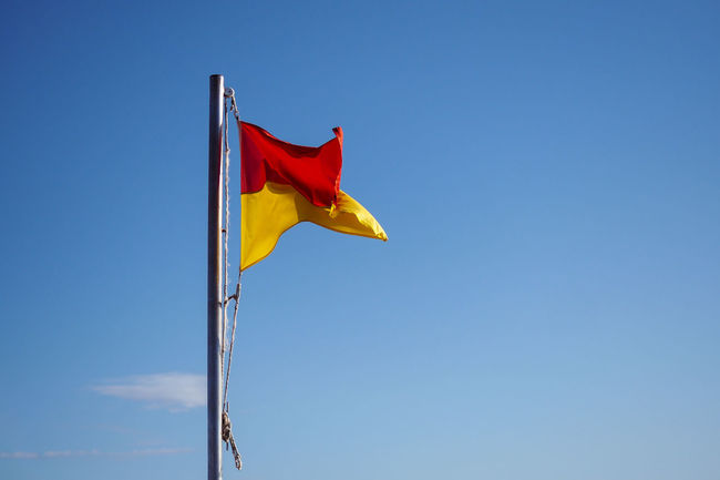 Beach Beach Flag Blue Blue Sky Clear Sky Day Flag Flags In The Wind  Fluttering Low Angle View No Clouds No People Outdoors Patriotism Red Red Flag Red Yellow Flag Sky Yellow Yellow Flag
