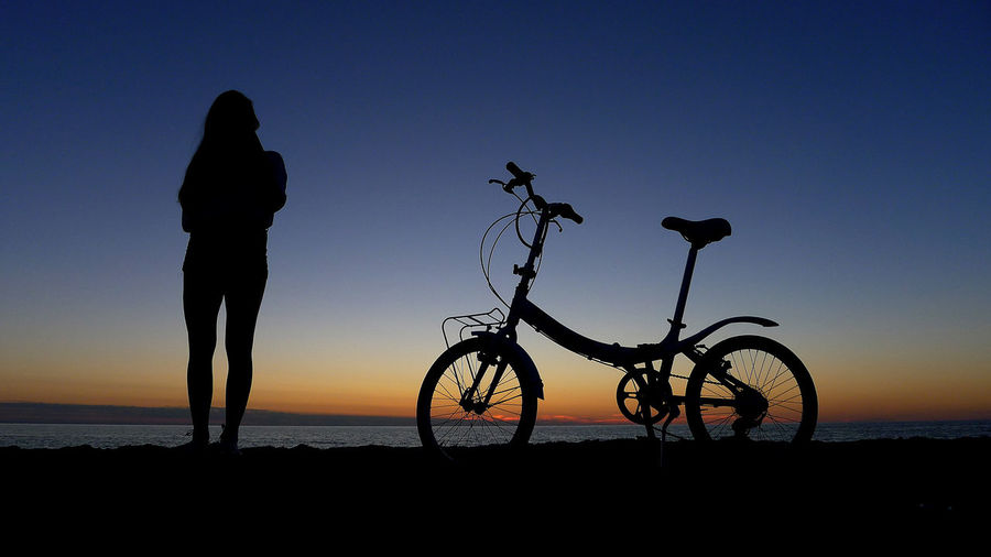 Silhouette person standing on bicycle by sea against sky during sunset