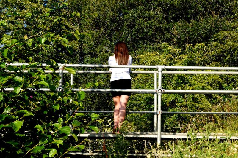 Woman standing on railing against trees