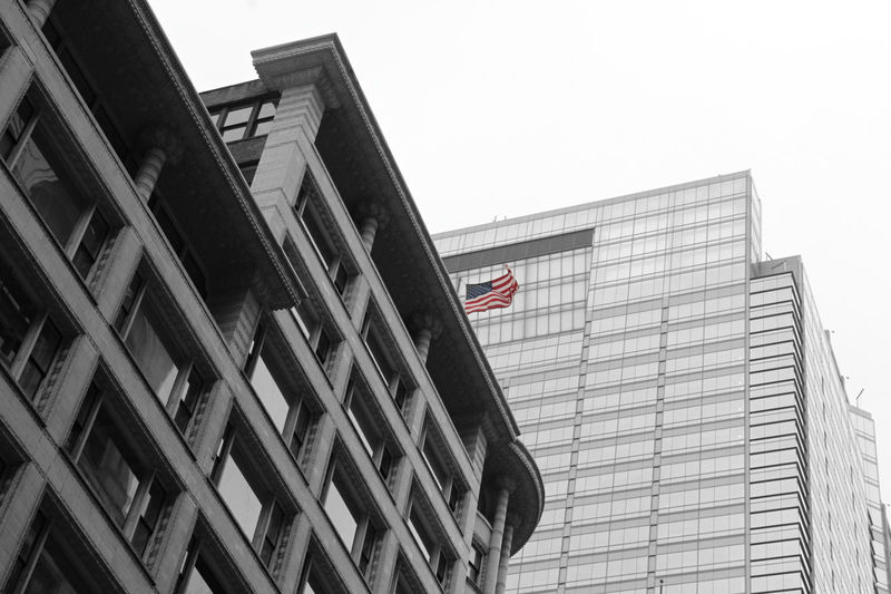 The American flag in a black and white shot of Chicago Chicago Chicago Architecture Low Angle View Architecture Built Structure Flag Patriotism Sky Building Exterior Building Clear Sky Office Building Exterior Day City No People Office Outdoors Tall - High Glass - Material Skyscraper American Flag Blackandwhite Black & White Urban Skyline Architecture