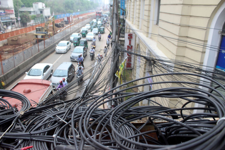 Cable Transportation Building Exterior Land Vehicle City Mode Of Transportation High Angle View Complexity Outdoors Motor Vehicle Street Wire Danger Dangerous Risky RISK Traffic Road Car Electricity  Electrical Equipment