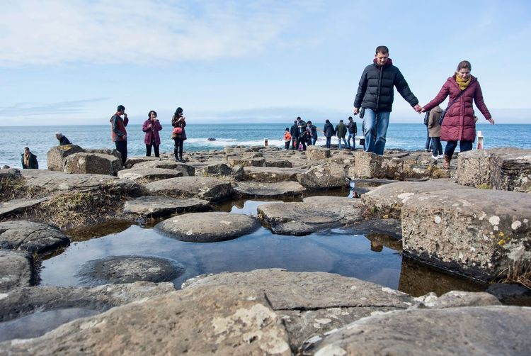 People standing on rocks by sea against sky