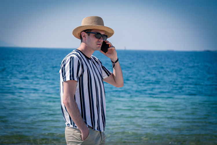 Relaxed man walking on the beach talking on the phone