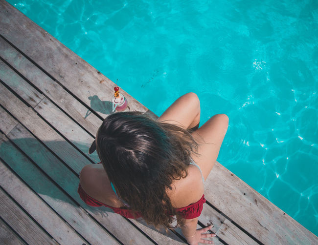 High angle view of woman sitting on swimming pool