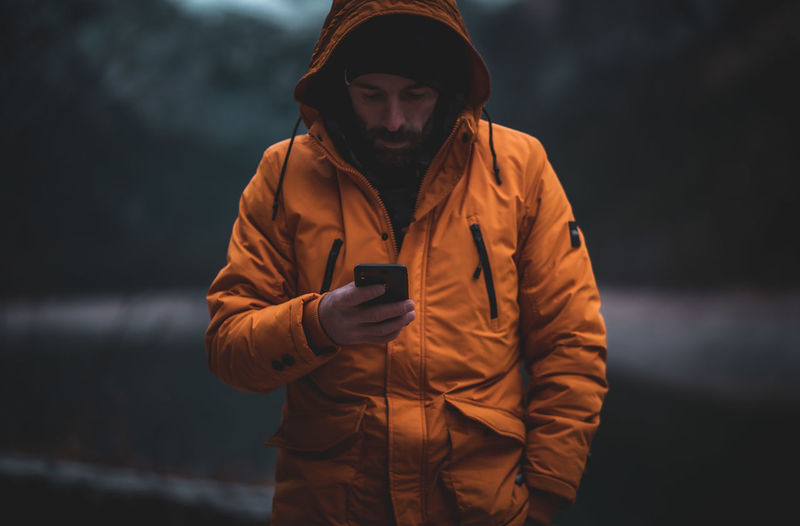 Man wearing jacket using smart phone while standing outdoors