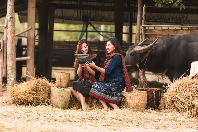 Smiling women using vintage radio while sitting at farm