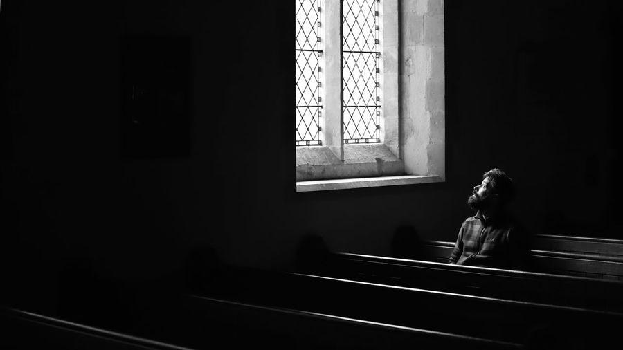 The light Chapel Church Pews Minimal Minimalism Light Soft Light Looking Solitary Seated Pews Church Man Window Indoors  Day The Minimalist - 2019 EyeEm Awards Architecture Sunlight Dark Glass - Material Representation Built Structure Belief Spirituality The Minimalist - 2019 EyeEm Awards
