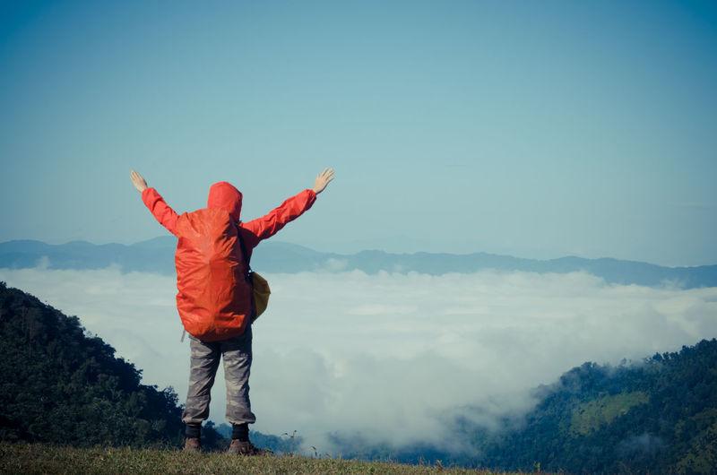 Full length of man standing on mountain against blue sky