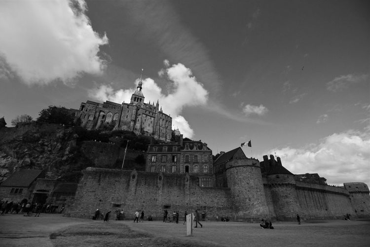 People in front of historical building against cloudy sky mont saint michel