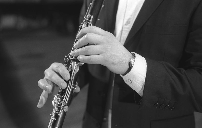 Midsection of man playing clarinet