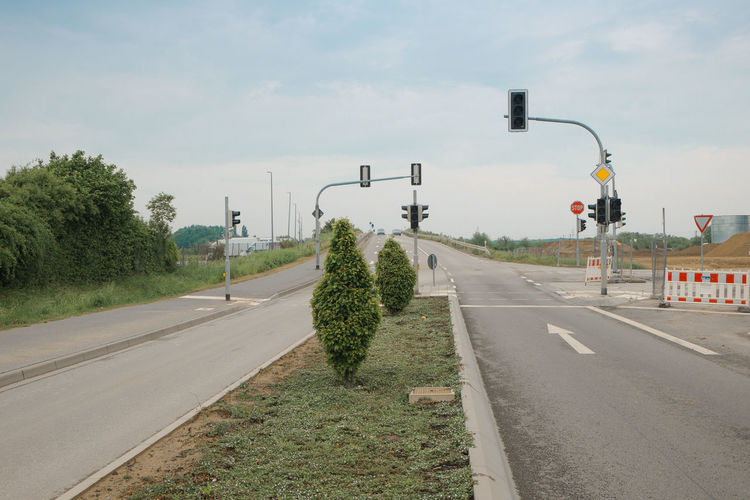 Auf dem Mittelstreifen City Cloud - Sky Day Diminishing Perspective Direction Dividing Line Empty Road Marking Median Nature No People Outdoors Plant Road Road Marking Sign Sky Street Street Light Symbol The Way Forward Traffic Lights Transportation Tree Tuja