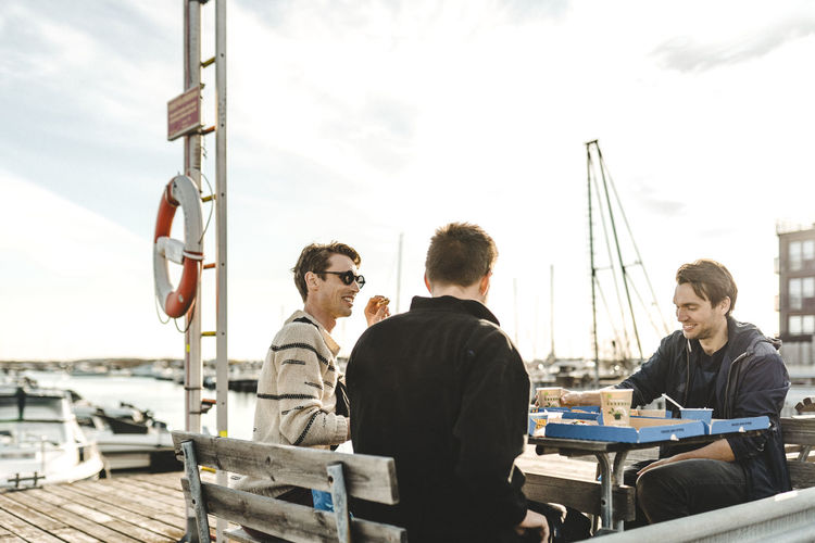 Men sitting on table at harbor against sky