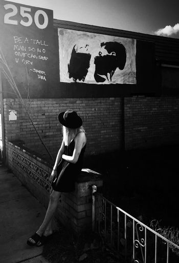 Full length of woman sitting on railing against wall