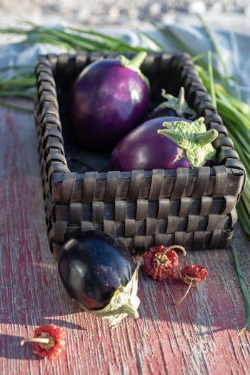 still life with basket, eggplants, garlic chives, dried red peppers Eggplant Homegrown Produce Ingredients Basket Chives Dried Peppers Eggplants Garlic Chives Organic Food Peppers Raw Food Still Life Tabletop Vegetable Vegetables