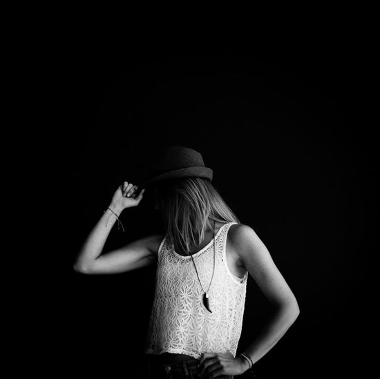Woman with covered face wearing hat against black background
