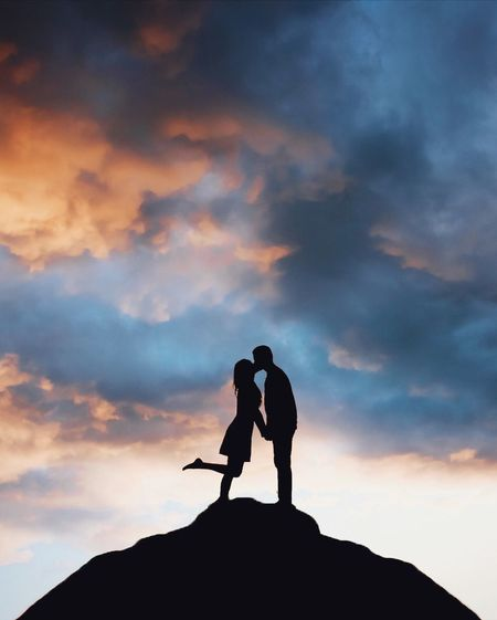 Low Angle View Of Silhouette Man Kissing Woman While Standing Against Sky During Sunset