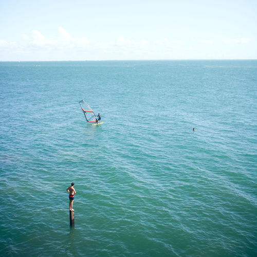 Boy looking at person windsurfing in sea against sky