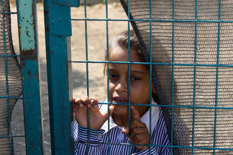 Midsection of child in cage