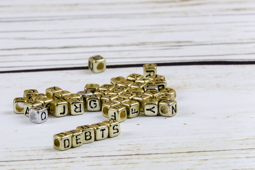 DEBT CONCEPT WITH GOLD DICE ON A WOODEN TABLE Capital Letter Close-up Communication Credit Card Debt Crisis Focus On Foreground Gold Colored High Angle View Indoors  Jewelry Key Large Group Of Objects Metal No People Pattern Personal Accessory Selective Focus Shape Still Life Table Text Western Script Wood - Material