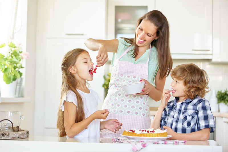 Happy woman by son feeding daughter red currents in kitchen