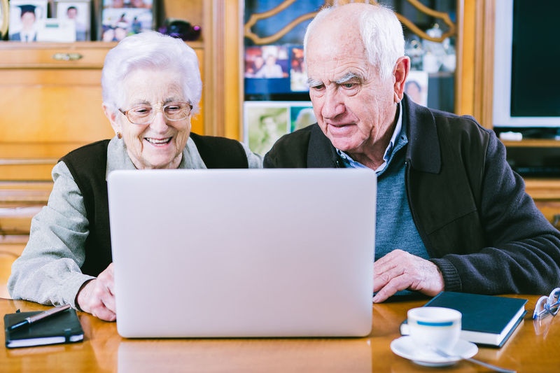 Couple of seniors surfing the net with a laptop at home. At Home Adult Bonding Communication Computer Day Eyeglasses  Indoors  Internet Laptop Leisure Activity Men Retirement Senior Adult Senior Couple Senior Men Senior Women Sitting Smiling Table Technology Togetherness Two People Using Laptop Wireless Technology