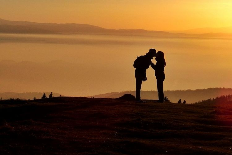 Silhouette Couple Kissing On Field Against Sky During Sunset