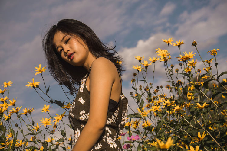 Beautiful Young Woman Standing Amidst Flowering Plants On Field Against Sky