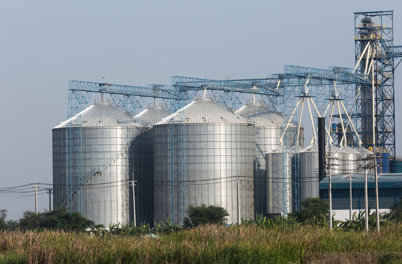 Storage Tank Sky Plant Industry Nature Silo Agriculture Factory Land Day Built Structure Architecture Clear Sky Container No People Grass Building Exterior Field Outdoors Storage Compartment Fuel Storage Tank Silver Colored Chemical Plant