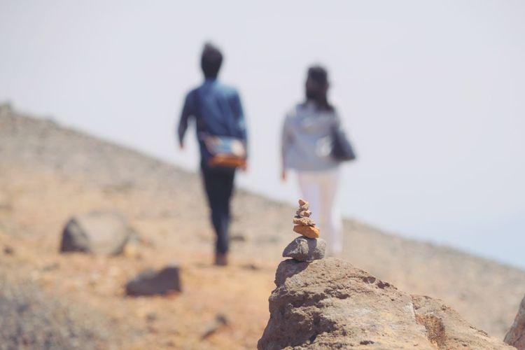 People walking on rock against sky