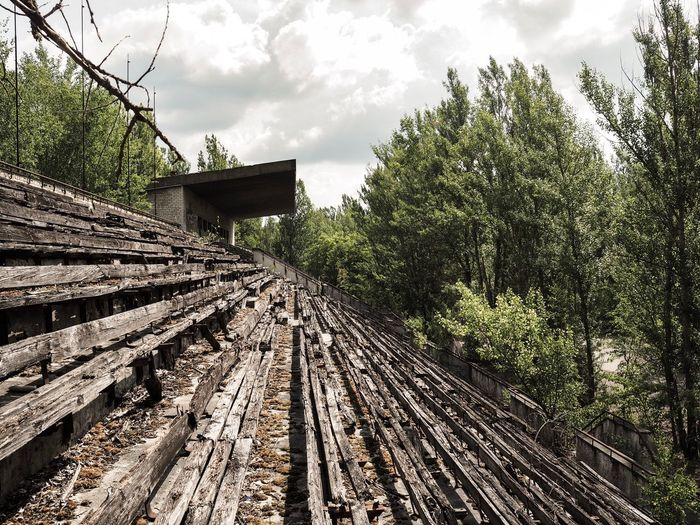 Abandoned structure in forest against sky