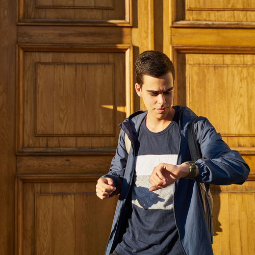 Young man looking away while standing against wooden wall