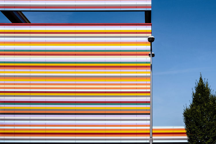 Multi Colored Architecture Low Angle View No People Built Structure Day Sky Nature Yellow Outdoors Clear Sky Tree Building Exterior Plant Pattern Striped Copy Space Red Wall - Building Feature Blue