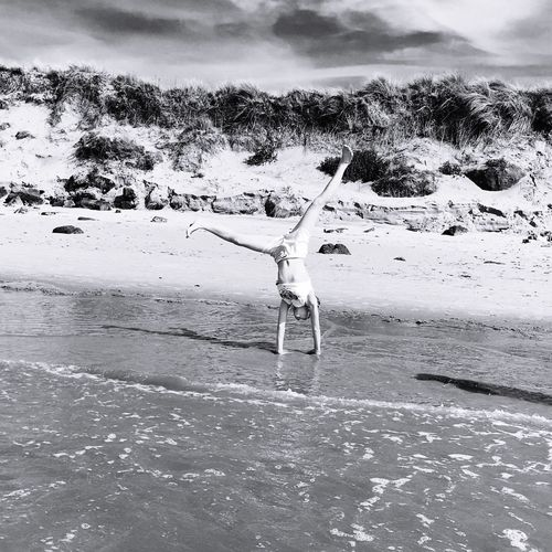 Woman performing cartwheel at beach on sunny day