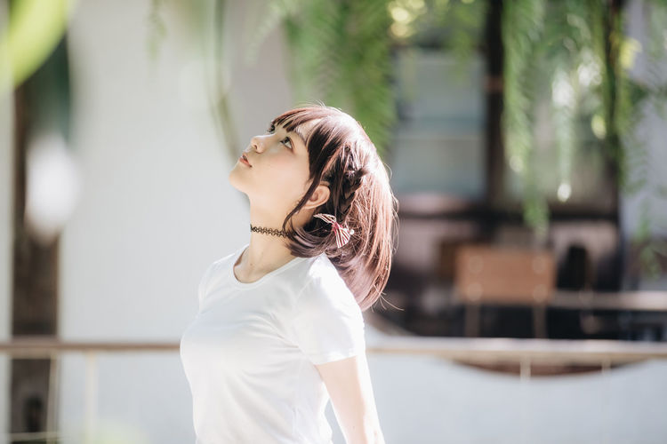 Side view of young woman looking away outdoors