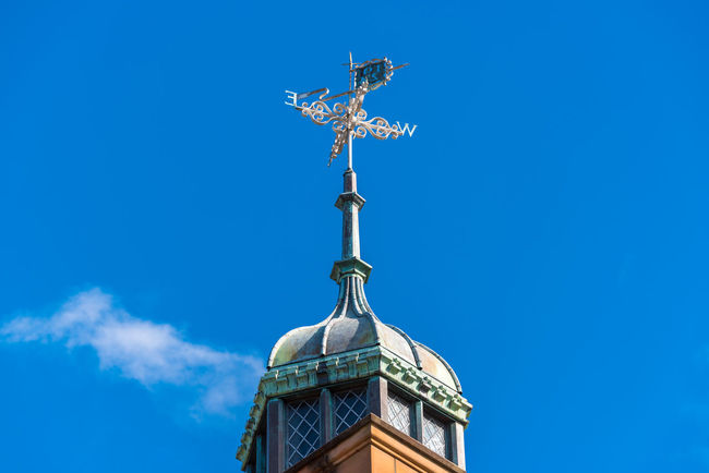 Vintage weather clock on top of old building against blue sky on the background Architectural Details Architecture Australia Camperdown Exterior Famous Gothic New South Wales  The Quadrangle University Of Sydney Weather Architectural Detail Building Historic Landmark Nsw Old School Sydney University Vintage Weather Vane
